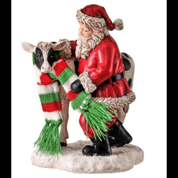 Santa putting scarf on cow figure