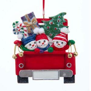 three snowmen in back of red truck
