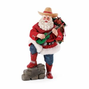A Cowboy Santa playing a guitar with his pack on his back and his foot on a bale of hay.