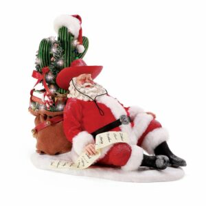 Snoring Cowboy Santa takes a nap as he leans against a decorated Christmas cactus.