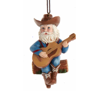 Cowboy Santa playing a guitar while sitting on a bale of hay ornament