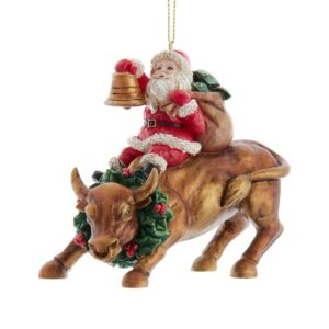 Santa Claus riding a gold bull with a wreath around its neck and ringing a bell ornament